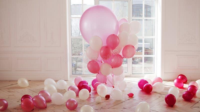 Lyxig vardagsrum med det stora fönstret till golvet Slotten fylls med rosa ballonger royaltyfri foto