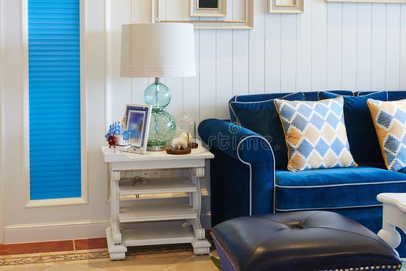 Lyxig vardagsrum med glass tabellljus för blå soffa hemma royaltyfri fotografi