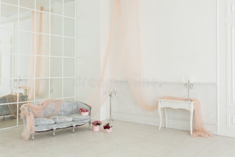 Lyxig vardagsrum med spegelväggen, tappningsoffan och tule för pastellfärgade rosa färger i en ny lägenhet dekorerade med blommab royaltyfria foton