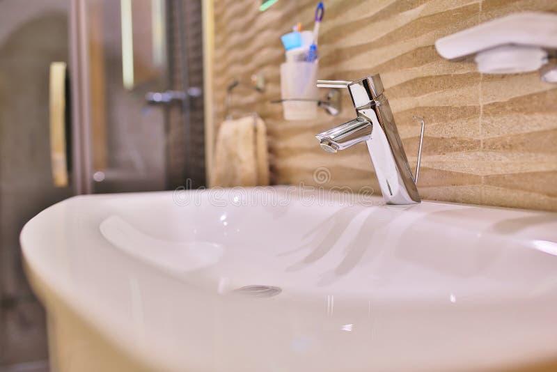 Lyxig vattenkranblandare p? en vit vask i ett h?rligt gr?tt inre badrum trevlig metallvattenkran i modernt badrum arkivfoto