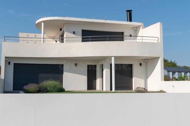Lyxig villa för modernt vitt hus med den gråa väggen i blå himmel royaltyfri bild