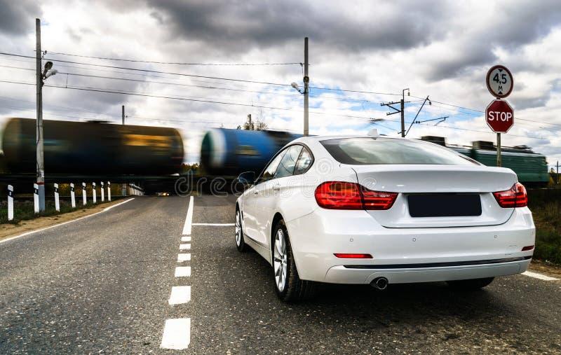 Lyxig vit bil som väntar på den järnväg korsningen royaltyfri foto
