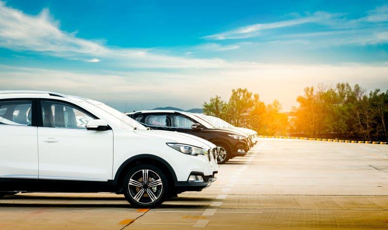 Lyxig vit och svart ny suvbil som parkeras på konkret parkeringsområde på fabriken med blå himmel och moln Till salu bilmateriel royaltyfri foto