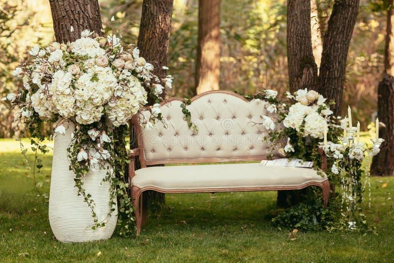 Lyxiga bröllopgarneringar med bänk-, stearinljus- och blommacompis arkivbild