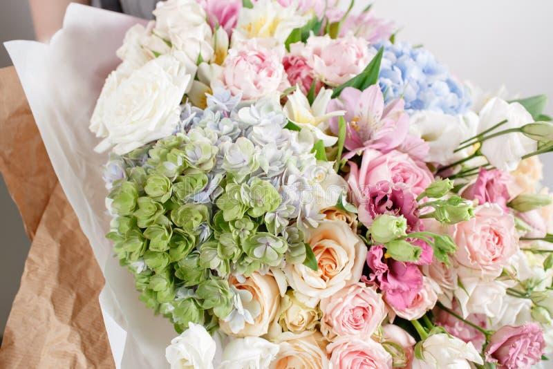 Lyxiga buketter av blandade blommor i handkvinnorna arkivfoton