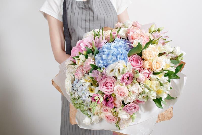 Lyxiga buketter av blandade blommor i handkvinnorna royaltyfri bild