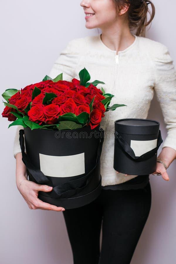 Lyxiga buketter av blommor i hatten boxas rosor i handkvinnorna Röd och svart färg royaltyfri bild