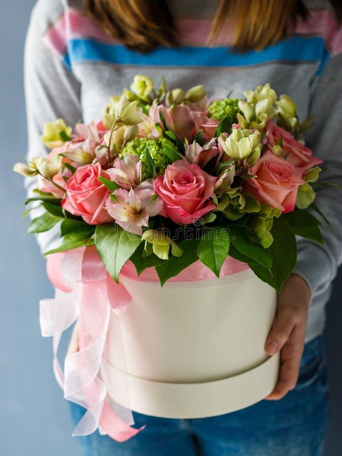 Lyxiga buketter av olika blommor i en hattask fotografering för bildbyråer
