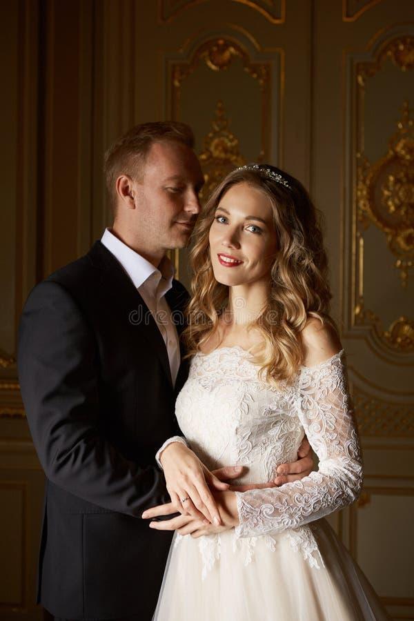 Lyxiga förälskade brölloppar Härlig brud i den vita klänningen med brudbuketten och stilig brudgum i svart dräkt royaltyfri bild