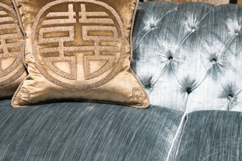 Lyxiga guldkuddar på den dyra blåa soffan royaltyfri bild