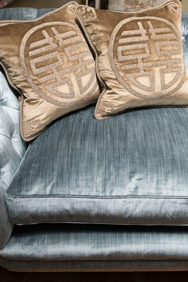 Lyxiga guldkuddar på den dyra blåa soffan fotografering för bildbyråer