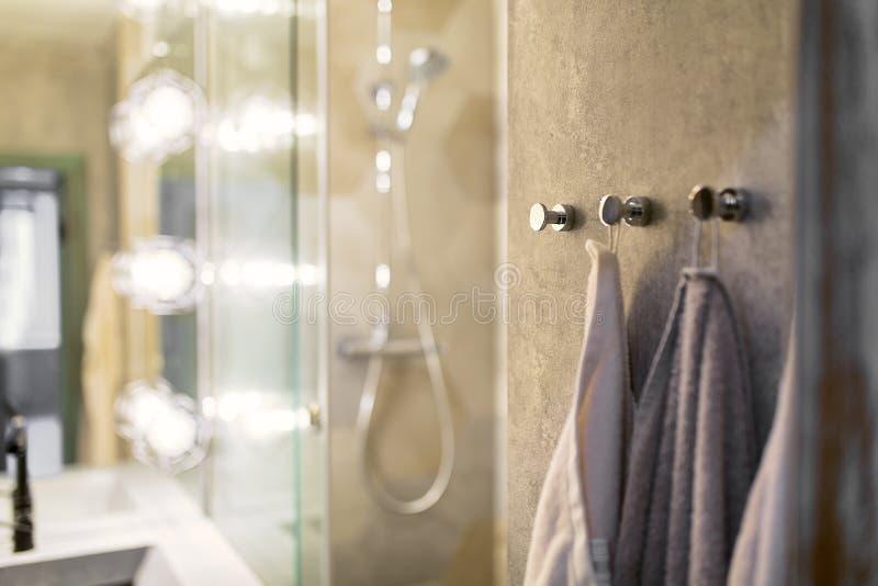 Lyxiga handdukar på oor hakar i modern bathroominframdel av spegeln royaltyfri foto