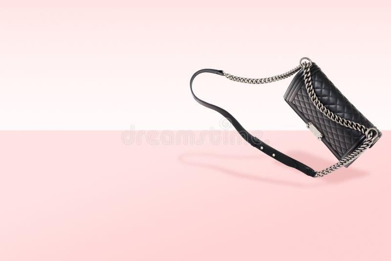 Lyxiga kvinnors handväska på rosa bakgrund Stålkedja och svart äktt läder med textur arkivbild