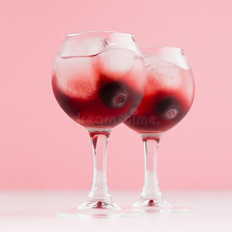 Lyxiga nya kalla röda sommarfruktcoctailar med iskuber, blåbär i elegant modern kökinre i mjuka pastellfärgade rosa färger royaltyfria foton