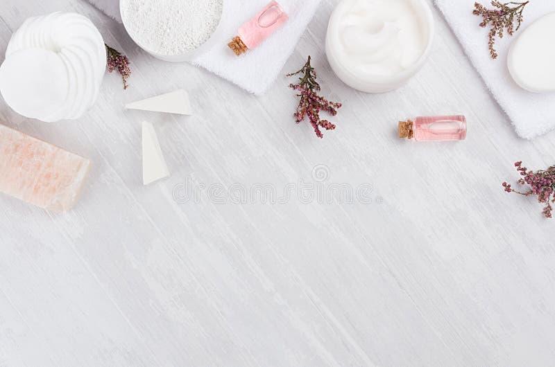 Lyxiga organiska skönhetsmedel för kropp- och hudomsorgbrunnsort som den dekorativa gränsen på vit wood bakgrund, lekmanna- lägen arkivfoto