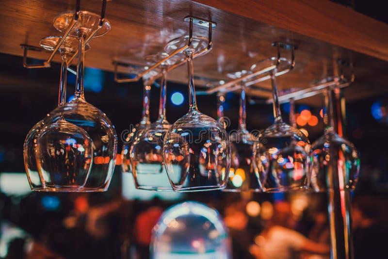 Lyxiga vin- och champagneexponeringsglas som hänger upp sida ner i baren royaltyfria foton