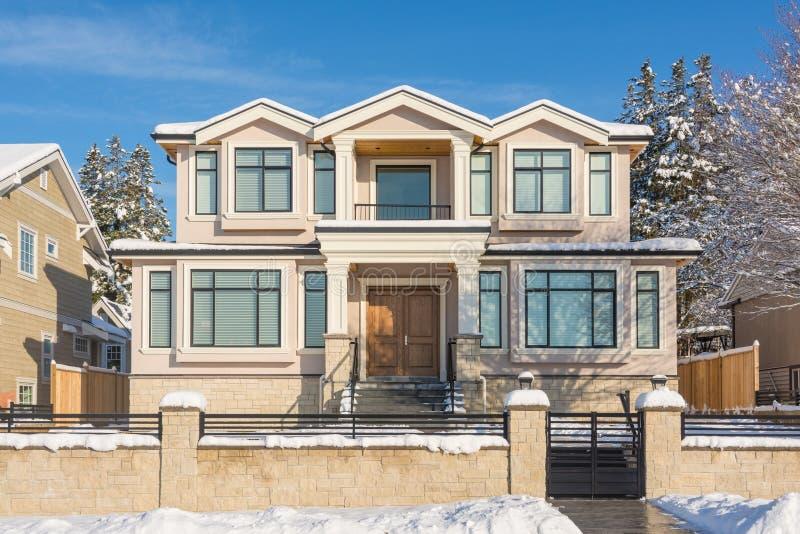 Lyxigt bostads- hus med den främre gården i snö på solig dag för vinter i Kanada arkivbild