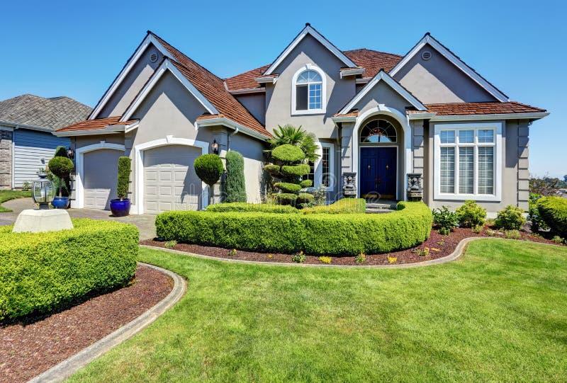 Lyxigt bostads- hus med den perfekt hållna framdelträdgården arkivfoton