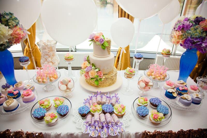 Lyxigt bröllop som sköter om, tabell med moderna efterrätter, muffin, sötsaker med frukter läcker godisstång på dyr gifta sig rec royaltyfri bild
