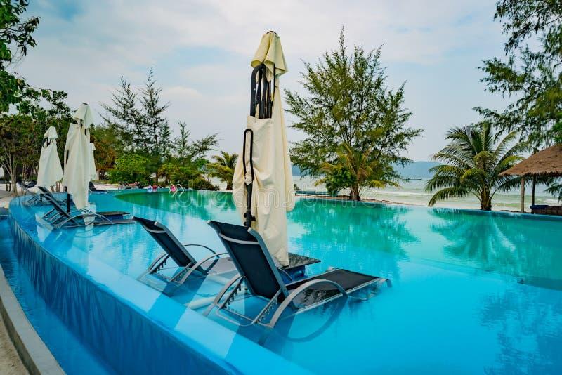 Lyxigt feriehotell för simbassäng som förbluffar sikt Koppla av nära pöl med ledstången, sunbeds, soldagdrivare och slags solskyd arkivfoton