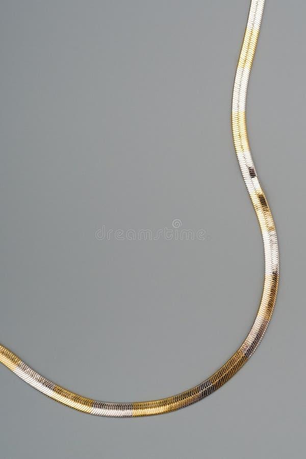 Lyxigt guld- halsband på grå färgbakgrund arkivfoto