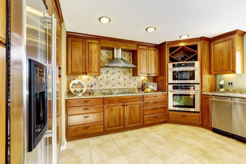 Lyxigt kök med tegelplattagolvet och nedfläckade kabinetter arkivfoto