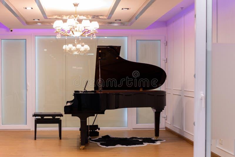 Lyxigt musikrum med flygeln och ljuskrona med färgrik belysning arkivfoton