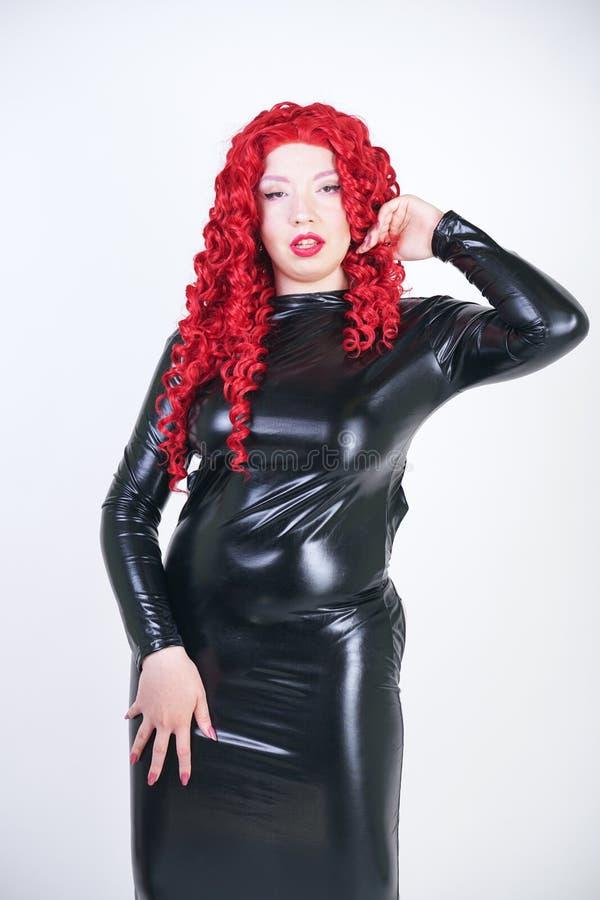 Lyxigt plus formatkvinna med den asiatiska framsidan, ljus makeup och rött lockigt hår som poserar i skinande stängd lång svart k arkivfoto