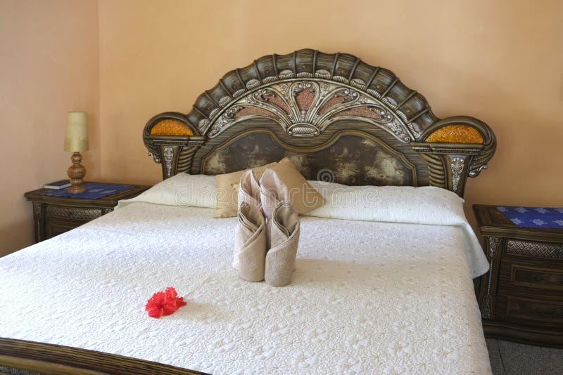Lyxigt sovrum som är inre med nya handdukar och den röda tropiska blomman på säng royaltyfri bild