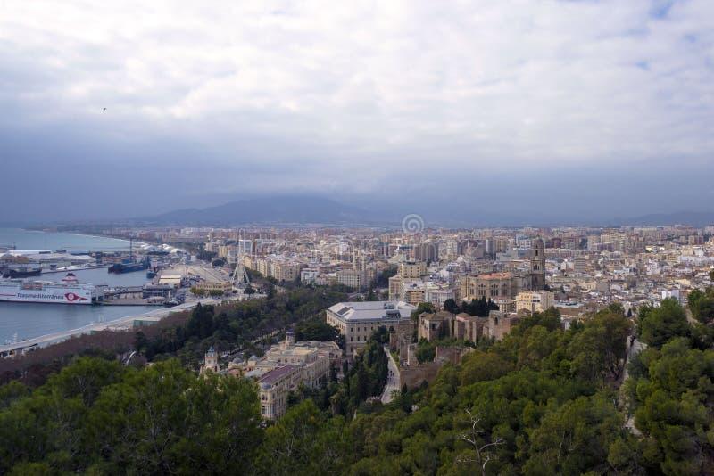 Màlaga, Spanien, im Februar 2019 Panorama der spanischen Stadt von Màlaga Gebäude, Hafen, Bucht, Schiffe und Berge gegen ein bewö lizenzfreie stockfotos