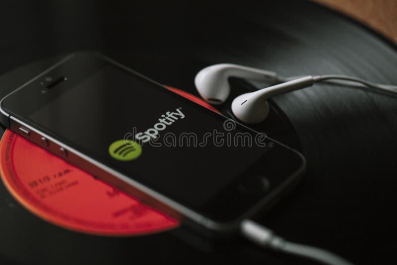 MÀLAGA, SPANIEN - 5. MÄRZ 2018: Handy mit Spotify-Musikservice auf dem Schirm und den weißen Kopfhörern auf einer schwarzen Vinyl stockfoto