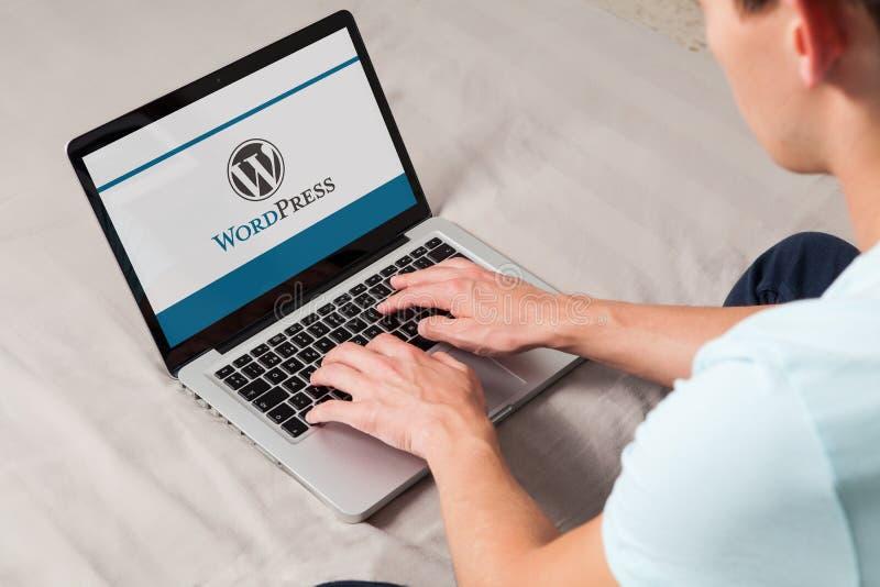 MÀLAGA, SPANIEN - 10. NOVEMBER 2015: Wordpress-Markenlogo auf Bildschirm Mann, der auf der Tastatur schreibt lizenzfreie stockbilder
