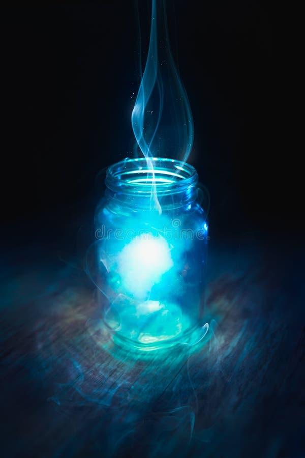 Mágica em um frasco em um fundo escuro fotos de stock royalty free