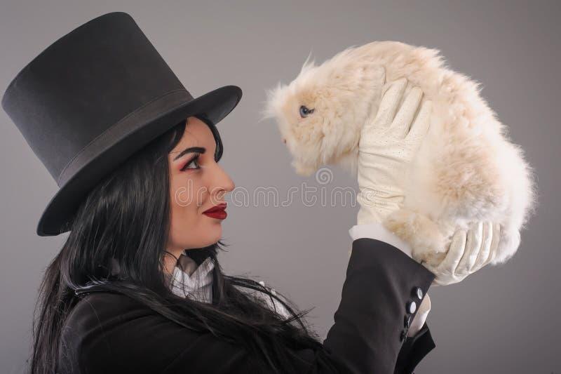 Mágico da jovem mulher com coelho branco bonito fotos de stock