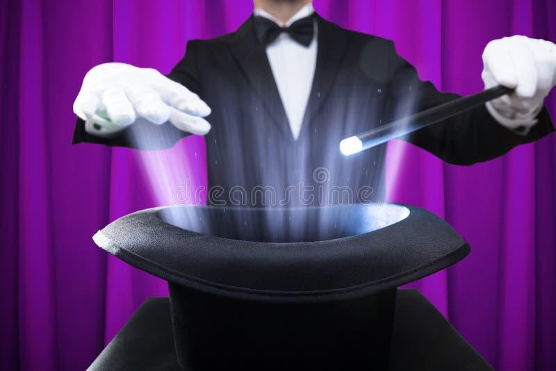 Mágico Holding Magic Wand sobre o chapéu iluminado fotos de stock