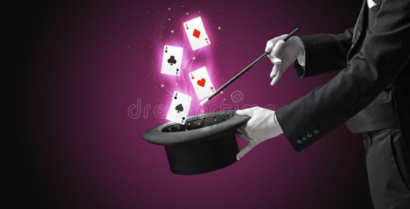 Mágico que faz o truque com os cartões da varinha e de jogo foto de stock