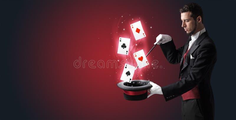 Mágico que faz o truque com os cartões da varinha e de jogo fotos de stock