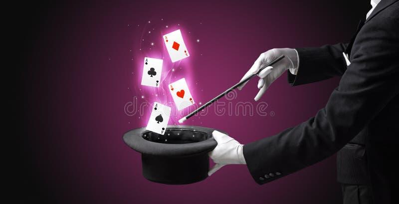 Mágico que faz o truque com os cartões da varinha e de jogo foto de stock royalty free