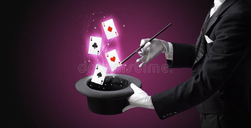 Mágico que faz o truque com os cartões da varinha e de jogo fotos de stock royalty free