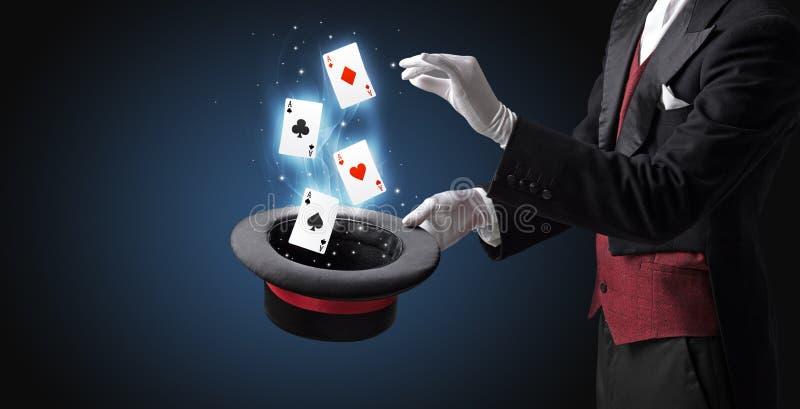 Mágico que faz o truque com os cartões da varinha e de jogo fotografia de stock