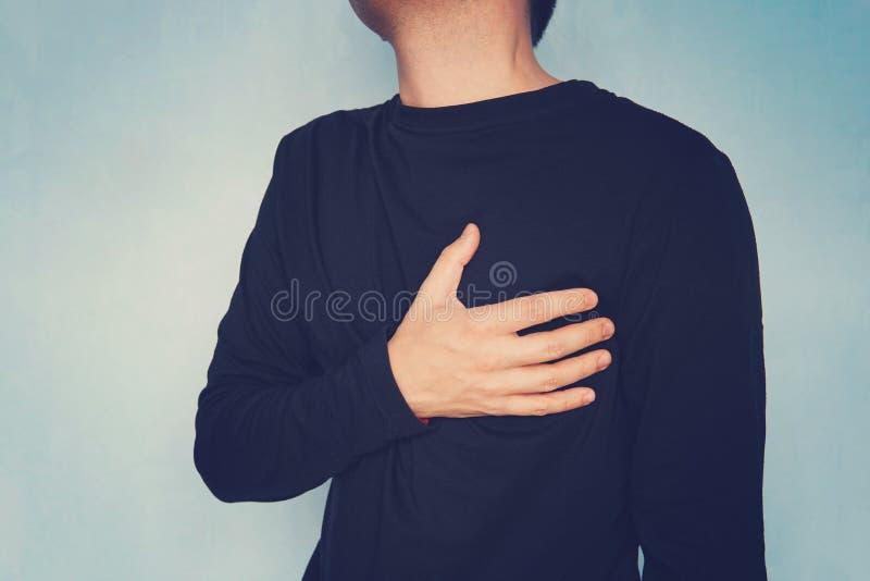 Mágoa, homem que sofre da dor no peito, tendo o cardíaco de ataque ou os grampos dolorosos, pressionando na caixa com expressão d imagem de stock