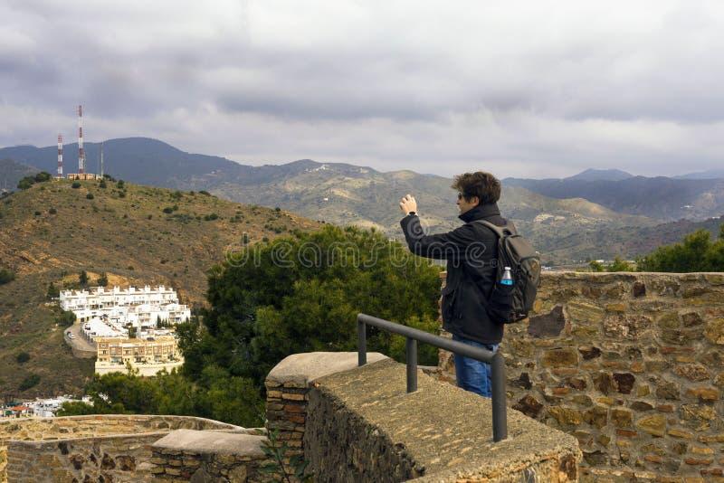 Málaga, España, febrero de 2019 Un hombre admira la ciudad española y toma las fotos Edificios, puerto, bahía, naves y montañas c fotos de archivo libres de regalías