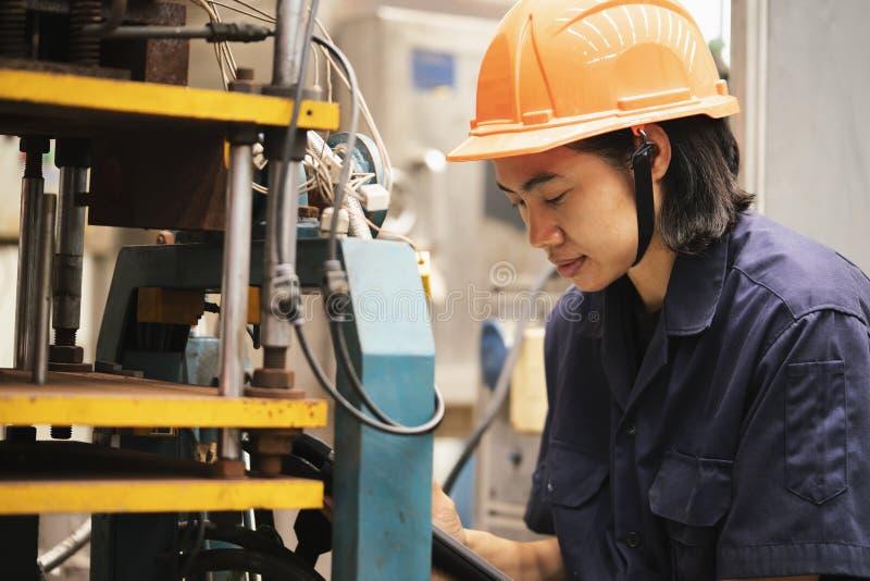 Máquina asiática joven de la disposición y de prueba del ingeniero de la mujer en la fábrica del laboratorio imágenes de archivo libres de regalías