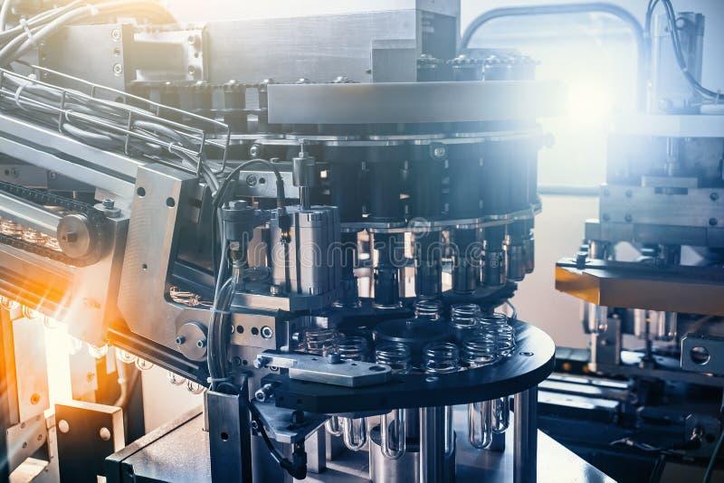 Máquina automatizada para fundir garrafas plásticas das pré-formas do ANIMAL DE ESTIMAÇÃO como o fundo industrial abstrato da fer imagens de stock royalty free