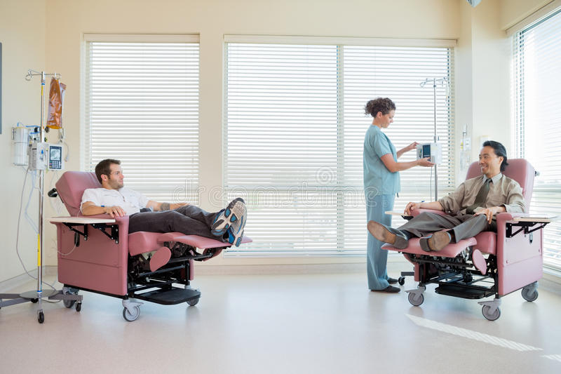 Máquina de Adjusting IV de la enfermera mientras que pacientes imágenes de archivo libres de regalías