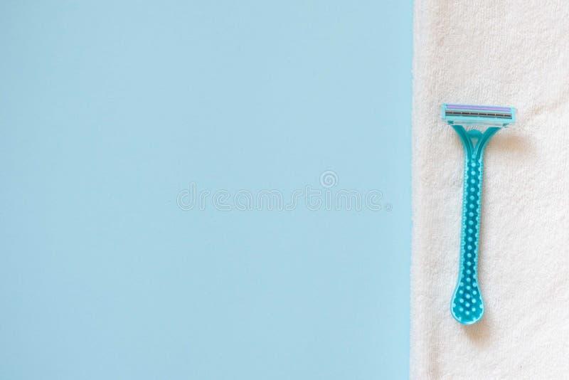 M?quina de afeitar azul con la trayectoria de recortes en la toalla blanca en fondo azul con el espacio de la copia Lugar para el imágenes de archivo libres de regalías
