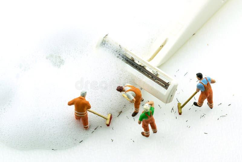 Máquina de afeitar blanca sucia de la limpieza miniatura de la gente en el fondo blanco fotos de archivo