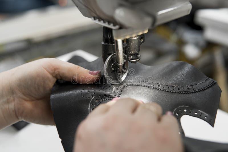 Máquina de costura em uma oficina de couro na ação com as mãos que trabalham no os detalhes de couro para sapatas As mãos das mul imagens de stock