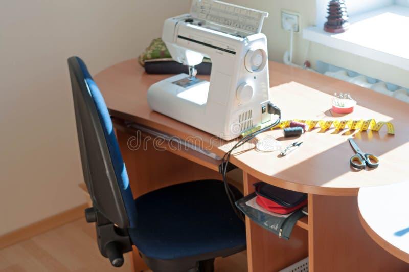 Máquina de costura, fita de medição, carretéis da linha e tesouras na tabela de madeira com luz solar imagens de stock royalty free