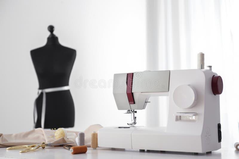 Máquina de costura moderna com fontes da tela e do alfaiate na tabela na oficina fotos de stock royalty free